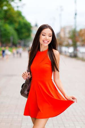 Vertical portrait of sweet and gorgeous Asian woman hold on to the hem of the dress and looks down against a blurred background of cityscape