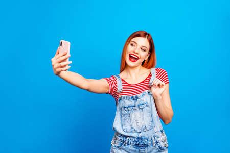 Portret van mooie levendige rode straight-haired opgewonden gelukkig lachend jong meisje met geopende mond nemen zelf foto, geïsoleerd op blauwe achtergrond Stockfoto