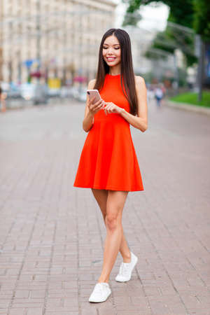 Full-size vertical portrait of pretty and calm Asian girl in red mini dress and white sneakers, with phone in hands strolling through the city on a sunny summer day Stockfoto