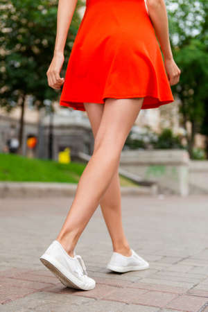 Cropped close up vertical low angle photo shot of slim woman legs in white footwear, walking on the paving stones