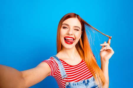 Portrait de beau rouge vif joyeux hétéro excité heureux souriant jeune fille avec la bouche ouverte en prenant la photo de soi, montrant la langue, isolé sur fond bleu Banque d'images