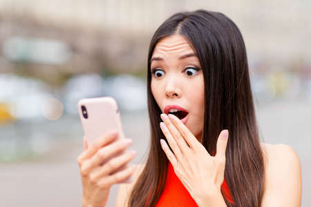 Young adorable and good-looking, Asian woman with dark hair is shocked by the SMS message, she opens her eyes wide and covers her mouth by hand