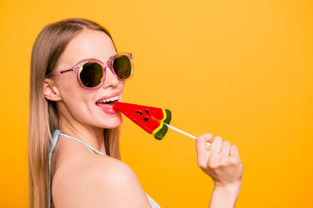 Attractive nice cute straight-haired beautiful smiling blonde girl, wearing blue swimsuit, color sun glasses, licking candy on stick. Copy space. Isolated over yellow background Stock Photo