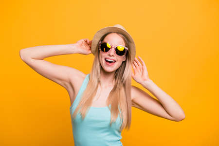Attractive nice cute straight-haired blonde caucasian smiling girl, wearing casual blue shirt, cap, sun glasses. Enjoying vacation. Isolated over yellow background