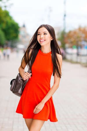 Vertical portrait of fascinating and young Asian woman in red mini dress and white sneakers against a blurred background of cityscape Stock Photo