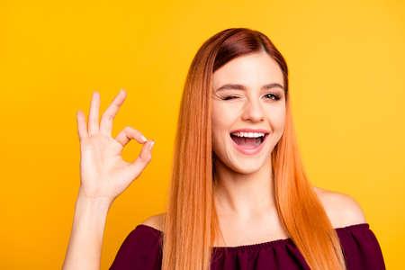 Lustiges und freudiges Mädchen zeigt okay Zeichen und zwinkert, Kamera betrachtend auf gelbem Hintergrund zu betrachten Standard-Bild