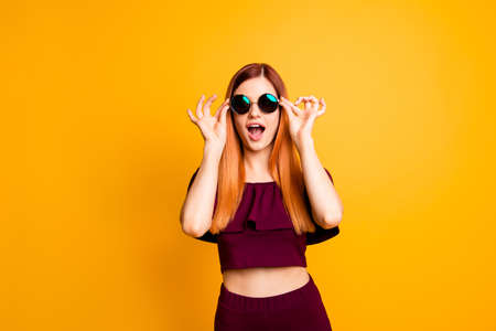 I can not believe it! The girl holds the glasses with both hands, opening her mouth in surprise isolated on yellow background 写真素材