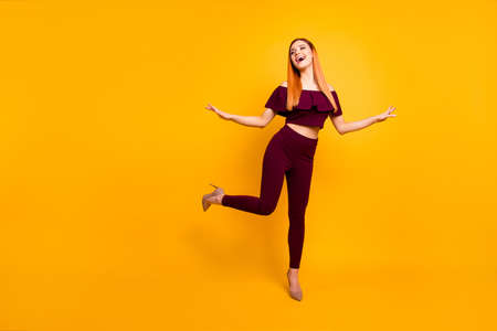 Full-size portrait of beautiful girl in beige shoes that stands one leg spreads joyfully hands isolated on yellow background with copy space for text Banco de Imagens