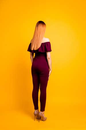Retrato de la sesión de fotos de la vista trasera a la mitad de la hermosa dama de cabello teñido de color largo con ropa de color marrón y zapatos de tacón beige aislados sobre fondo brillante Foto de archivo