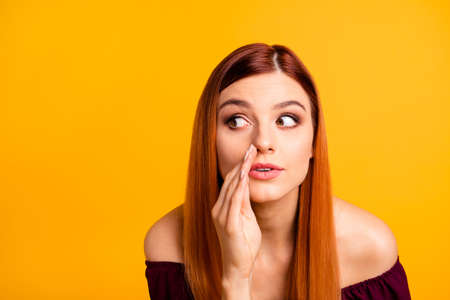 Close up portrait of  young girl tells a gossip secretly looking away and putting her hand to her mouth isolated on yellow background Stock Photo