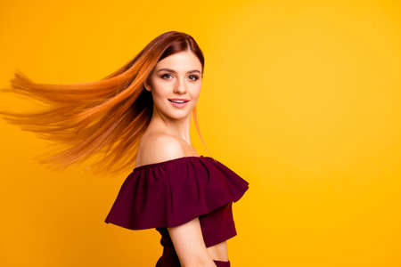 Red straight-haired attractive cute nice cheerful young girl, half turned, wind blowing hair. Isolated over bright vivid yellow background Imagens