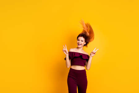 Red straight-haired attractive cute nice cheerful young girl, half turned, wind blowing hair up in air, showing double v-sign. Isolated over bright vivid yellow background Imagens
