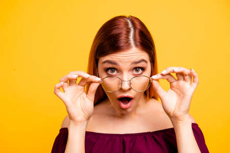 Close up photo portrait of attractive pretty clever intelligent shocked geek nerd lady adjusting touching round spectacles isolated on bright background