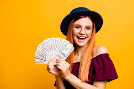 Cute and happy young woman in hat and glasses looks at camera with lot of money in the hands isolated on yellow background 写真素材
