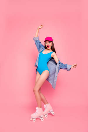 Full-legs portrait vertical of cute and funky girl in a denim shirt on roller skates isolated on vivid pink background Stock Photo