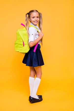 Longitud total, piernas, cuerpo, tamaño de perfil vertical Foto de vista lateral de una niña pequeña alegre, linda y agradable en falda aislada sobre fondo amarillo brillante se encuentra a media vuelta y mira por encima del hombro en la cámara