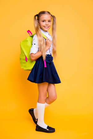 Full length, legs, body, size vertical profile side view photo of gorgeous, good-looking small girl in skirt stand half a turn isolated on yellow background hold backpack on shoulder Foto de archivo