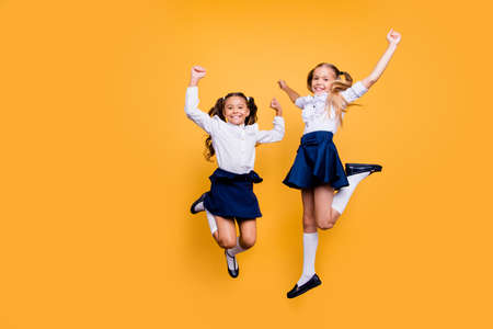 Dynamic images. Motion, movement, action concept. Full length, legs, body, size portrait of carefree, careless, adorable, beautiful, small girls jumping isolated on yellow background Foto de archivo - 107150932
