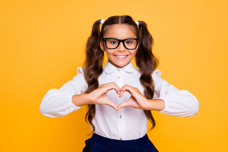 Portrait of cheerful, joyful, nice, lovely, sweet small brunette girl isolated on yellow background makes heart with her hands