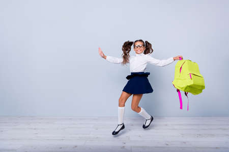 Back to school concept. Full length, legs, body, size portrait of cheerful, cute, nice, lovely, sweet girl in blue skirt, white blouse and yellow rucksack jumping isolated on light gray background