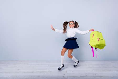 Concepto de regreso a la escuela. Longitud total, piernas, cuerpo, tamaño retrato de niña alegre, linda, agradable, encantadora y dulce con falda azul, blusa blanca y mochila amarilla saltando aislado sobre fondo gris claro