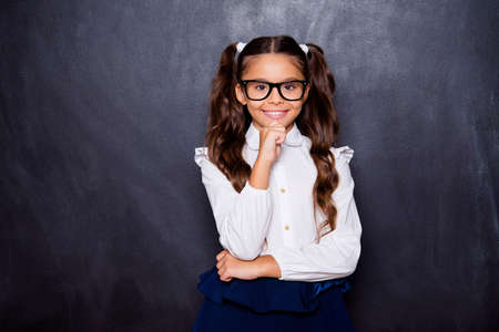 Portrait of positive glad nice adorable cute small little girl with curly ponytails in white formal blouse shirt, skirt, touching chin. Isolated over black background Stock fotó
