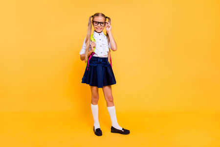 Full length, legs, body, size portrait of sweet, small blonde girl stand isolated on shine yellow background with copy space for text corrects glasses and looks directly at the camera