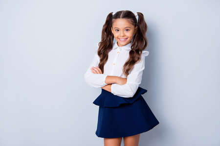 Back to school! Nice cute tender cheerful adorable lovely stylish girl with curly pony-tails in white formal blouse and dark blue skirt, folded arms. Isolated over grey background Archivio Fotografico