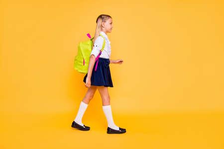 1 september concept. Volledige lengte, benen, lichaam, grootte verticaal profiel zijaanzicht foto van klein meisje geïsoleerd op gele achtergrond met gele rugzak op schouders Stockfoto