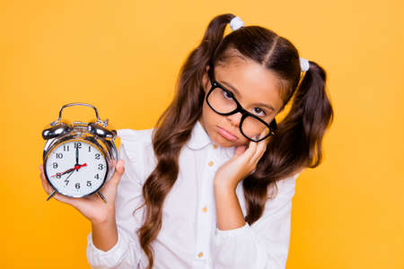 Close up portrait of sad, lazy, indifferent small brunette girl with watch in hands, in black glasses with modern hairstyle isolated on shine yellow background Banco de Imagens