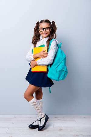 Full size body length of cute cheerful lovely stylish adorable small little girl with curly pigtails in white blouse shirt and blue skirt, holding color book pile, folders. Isolated on grey background
