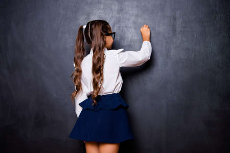 Back rear view of nice genius adorable lovely small little girl with curly ponytails in white formal blouse shirt, blue skirt, writing on blackboard. Isolated over black background Stock Photo