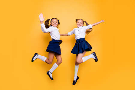 Dynamic images. 1-september concept. Full length, legs, body, size portrait of careless, cheerful, small girls in dark blue skirt, white blouse and black shoes jumping isolated on yellow background