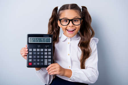 Portrait of funny cute cheerful lovely stylish girl with curly pigtails in white formal blouse shirt, showing numerals, numbers on calc. Isolated over grey background Stock Photo