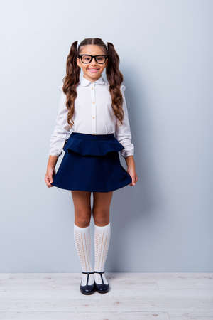 Full body size length of nice cute cheerful adorable lovely stylish little small girl with curly ponytails in white formal blouse shirt, short blue skirt. Isolated over grey background Foto de archivo