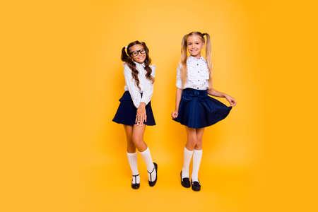 Volle Länge, Beine, Körper, Größenporträt von fröhlichen, niedlichen, netten, reizenden, süßen, entzückenden kleinen Mädchen stehen isoliert auf lebendigem gelbem Hintergrund