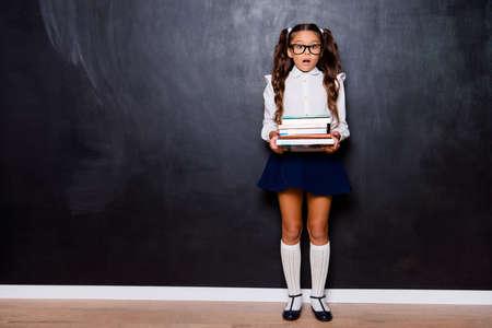 Volledige lichaamslengte van vermoeide, mooie, slimme, schattige kleine meid met gekrulde staartjes in een wit blouseoverhemd en een blauw kort rokje, met een zware stapel boeken. Geïsoleerd op zwarte achtergrond Stockfoto