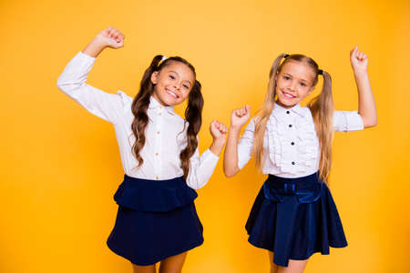 Portrait of beautiful small girl isolated on vivid yellow background looking into the camera joyfully lifting their fists upwards
