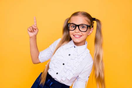 Zurück zur Schule! First Grade Junior Lifestyle Teen Konzept. Schließen Sie herauf Studio-Foto-Porträt des niedlichen Mädchens, das tragendes weißes Outfit der trendigen Bluse gestikuliert, isolierte hellen Glanzhintergrund Standard-Bild