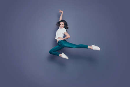 Crazy adorable attractive pretty stylish trendy nice lovely cheerful curly-haired brunette girl in casual white t-shirt and jeans, fooling around in air, dancing, isolated on grey background