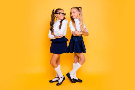 Full length, legs, body, size portrait of beautiful, pretty, charming, lovely, sweet small girls stand back-to-back with crossed arms took to each other isolated on shine yellow background Banque d'images - 107151374