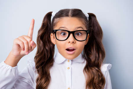 Close-up portrait of nice cute minded funny adorable lovely stylish small little girl with curly pigtails in white formal blouse shirt, wearing glasses, pointing up. Isolated over grey background 免版税图像