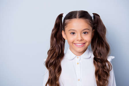 First grade schoolkid. Portrait of nice cute cheerful positive latin ethnicity girl with curly pigtails in white formal shirt. Copy-space, isolated over grey background