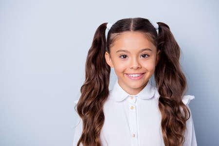 Schulkind der ersten Klasse. Porträt des netten niedlichen fröhlichen positiven lateinamerikanischen ethnischen Mädchens mit den lockigen Zöpfen im weißen formellen Hemd. Kopierraum, isoliert über grauem Hintergrund
