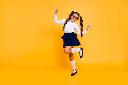 Im happy because Im going back to school! Full length, legs, body, size portrait of small girl isolated on bright yellow background stands on one leg raised her hands up 写真素材