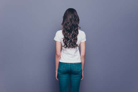 Rear back behind view of attractive pretty adorable stylish curly-haired girl in jeans and t-shirt, isolated over grey background