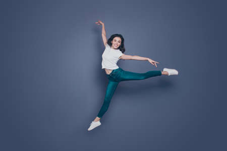 Graceful magnificent attractive pretty stylish trendy nice lovely cheerful curly-haired brunette girl in casual white t-shirt and jeans, flying in air, dancing like ballet, isolated on grey background