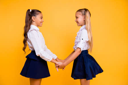 Profile side view photo of beautiful, charming, gorgeous, adorable small girls isolated on shine yellow background holding hands and looking at each other smiling