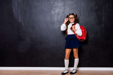 Full size body length of glad content nice smart cute small little girl with curly pigtails in white blouse shirt and blue short skirt with red bag, touching glasses. Isolated over black background Stockfoto