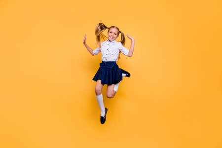 Full length size studio photo portrait of pretty beautiful cheerful excited nice glad satisfied in white shirt blue skirt schoolkid gesturing hands jumping up isolated bright background